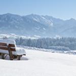 Bank im Tiefschnee mit Blick auf die Allgäuer Berge