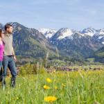 Urlaubspaar in grüner Wiese mit schneebedeckten Bergen