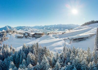 Allgaeuer Berghof Westseite mit Neubau - Luftaufnahme im Winter